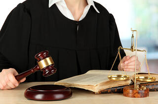 bigstock-Judge-sitting-at-table-during--42511381.jpg