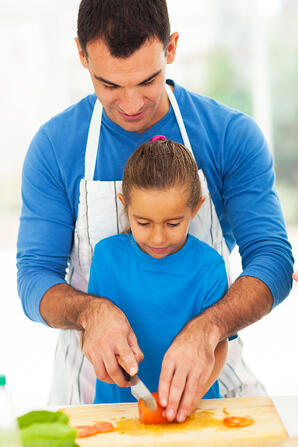 Divorced man teaching daughter to cook
